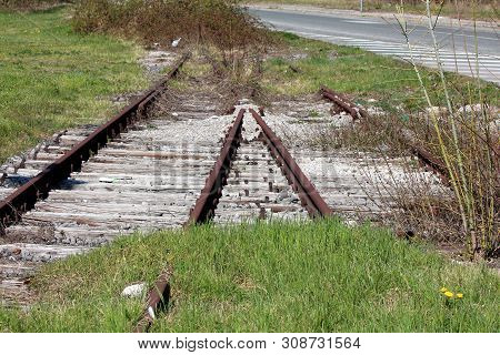 Overgrown Old Unused Rusted Railroad Tracks Resting On Wooden Railroad Ties Next To Paved Road On Wa