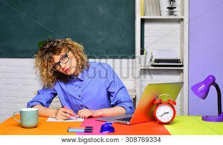 Young teacher in glasses over green chalkboard background. Female university student sits on desk. Surprised girl student or woman teacher sits at table. Exam in college. University student at campus. poster