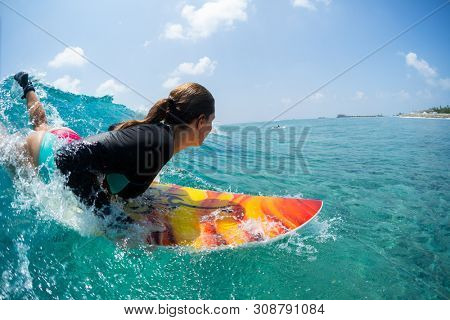Young woman surfer takes off and starts riding the ocean tropical wave. The surf spot named Chickens in Maldives