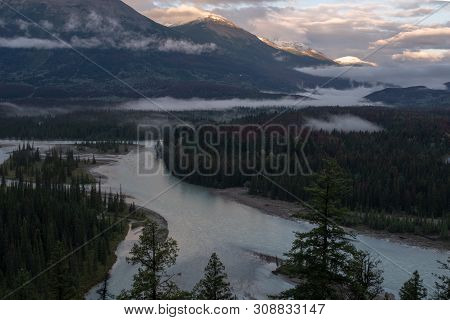 A View Of The Athabasca River As It Weaves Its Way Through The Jasper National Park, Canada On A Clo