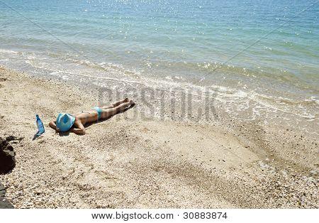 A woman sunbathing on beach
