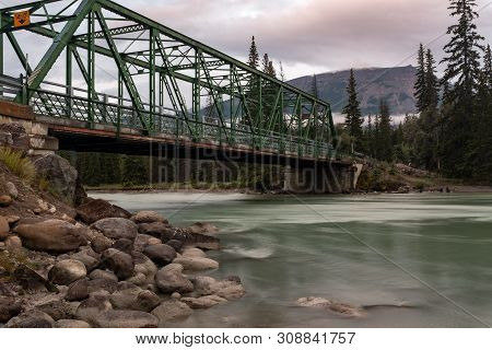 A Green Iron Metal Bridge Across The Athabasca River In Jasper National Park, Waters Are Smooth Due