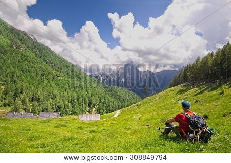Hiker Sitting On The Lawn Admires The Mountain Panorama.
