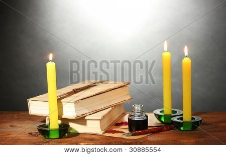 old books, scrolls, ink pen inkwell and candles on wooden table on grey background poster