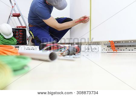 Electrician At Work With Pencil And Meter Measures On The Wall The Position For The Electric Socket,