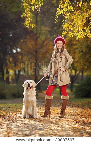 Smiling young woman with her labrador retreiver dog in a city park