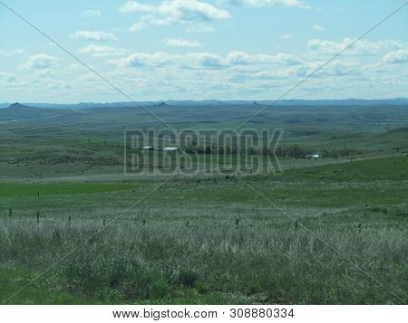 vast open grazing pasture land with farm buildings and mountains in the background under a blue and cloudy sky in big sky county poster
