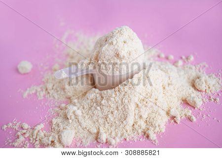Heap Of Whey Protein Powder With Plastic Spoon On Pink Background