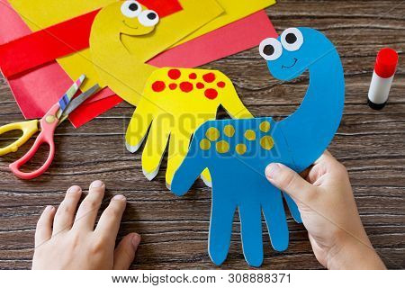 The Child Holds Father's Day Or Birthday Gift - Card Dinosaur. Handmade. Project Of Children's Creat