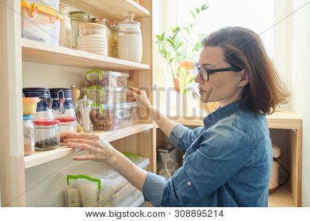 Interior Of Wooden Pantry With Products For Cooking. Adult Woman Taking Kitchenware And Food From Th