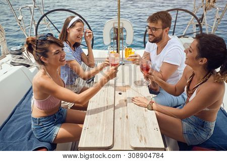 Happy friends toasting drinks on the yacht deck and laughing. Cheerful men and woman partying on a boat.