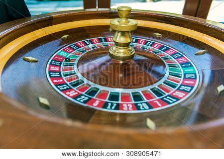 Roulette Table Wheel And Ball With Markings For Players To Place Their Wagers And Hopes To Gamble A