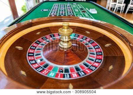 Roulette Table Wheel And Long Table With Markings For Players To Place Their Wagers And Hopes To Gam