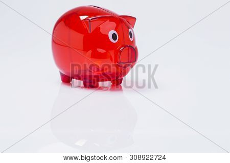 The Image Shows A Red Piggy Bank, Isolated On White Background