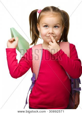Portrait of little schoolgirl with backpack thinking about something and going to throw a paper airplane, isolated over white
