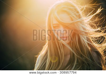 poster of Adding volume to her long hair. Sensual woman with wavy long hair outdoor. Pretty girl with beautiful healthy hair in sunlight. Trendy hairstyles for long hair, copy space.