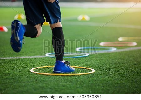 Selective Focus To Kid Soccer Player Jogging And Jump At Ring Ladder Marker On Green Artificial Turf
