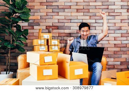 Young Asian Happy Male Business Entrepreneur Using Computer Laptop While Packing Products Into Boxes