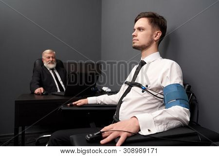 Serious Man Telling Truth During Lie Test On Detector. Young Man In White Shirt Sitting On Chair Wit