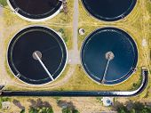 Modern wastewater treatment plant, top view from drone, sedimentation drainage tanks round form. poster