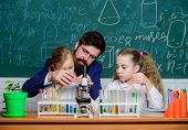 Explaining biology to children. How to interest children study. Fascinating biology lesson. Man bearded teacher work with microscope and test tubes in biology classroom. School teacher of biology poster