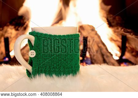 Green Knitted Sweater On Coffee Mug On White Fur By Fireplace
