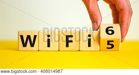 Wifi 5 Or 6 Symbol. Businessman Turns A Wooden Cube And Changes The Words Wifi 5 To Wifi 6. Beautifu