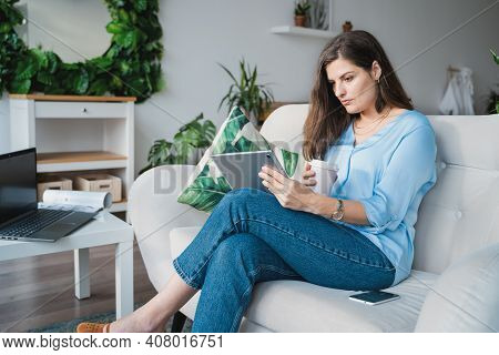 Business Woman In Blue Shirt Typing In Tablet.online Conference.remote Work At Home Office Sitting O