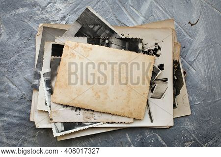 Stack Old Photos  On Grey Background.  Postcard Rumpled And Dirty Vintage. Retro Card