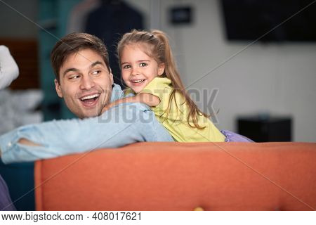 Joyful father and daughter playing together at home