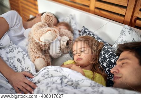 Happy parents sleeping together with kids in the bed