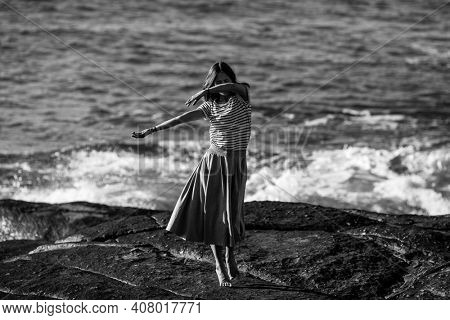 Young dance woman is engaged in choreography on the ocean coast. Black and white photo.