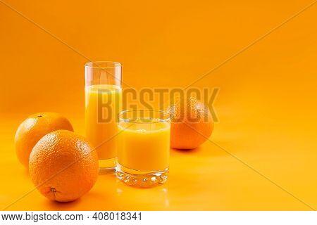 Natural 100% Orange Juice. Fresh Oranges And Orange Juice In Glasses On An Orange Background. Still