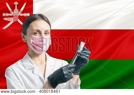 Girl Doctor Prepares Vaccination Against The Background Of The Oman Flag. Vaccination Concept Oman.
