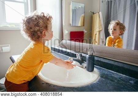 Little Caucasian Boy Toddler Washing Hands In Bathroom At Home. Health Hygiene And Morning Routine F
