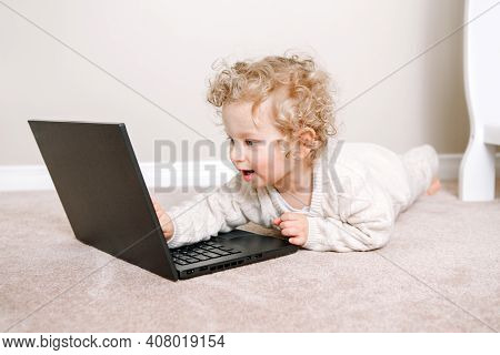 Cute Blonde Curly Toddler Baby Boy Working On Laptop. Little Kid Child Using Technology. Early Age E