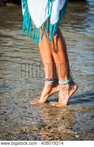 barefoot boho woman legs in river  shallow with  ankle bracelet  and toe rings white dress with tassels close up summer day