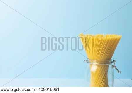 Spaghetti Pasta On A Blank Blue Background. Raw Fresh Isolated Spaghetti In A Jar Before Preparing I
