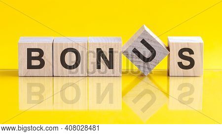 Bonus Word Written On Wood Block. Bonus Word Is Made Of Wooden Building Blocks Lying On The Yellow T