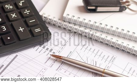 Desktop Of Businessman, Student, Accountant. Paper, Financial Report, Pen, Notepad, Flash Drive On A