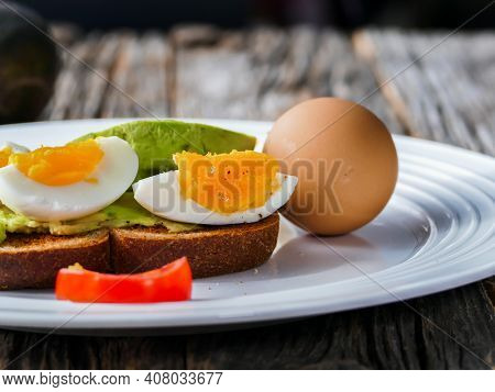 Toast with avocado and eggs on plate