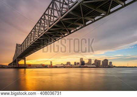 New Orleans, Louisiana, USA at Crescent City Connection Bridge over the Mississippi River at sunset.