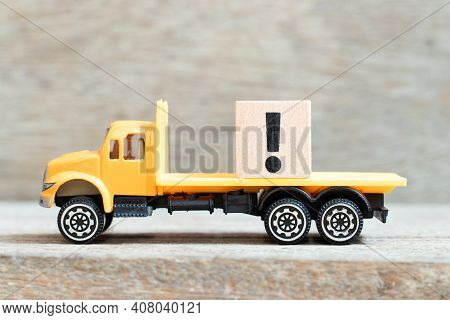 Toy Truck Hold Alphabet Letter Block In Exclamation Mark Sign On Wood Background