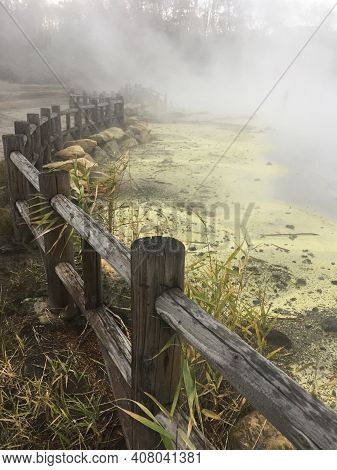 Steam Rises From A Hot Spring Pool Ringed By Yellow Sulphur And Surrounded By A Fence