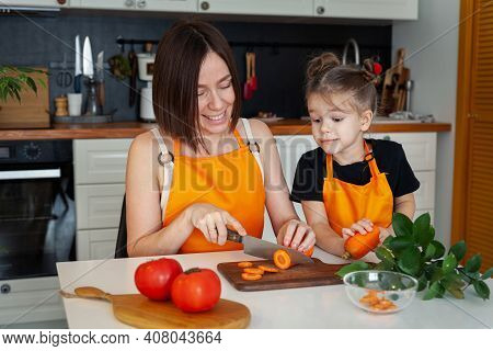 Little Girl And Beautiful Mom Are Cooking Vegetables At Home Kitchen