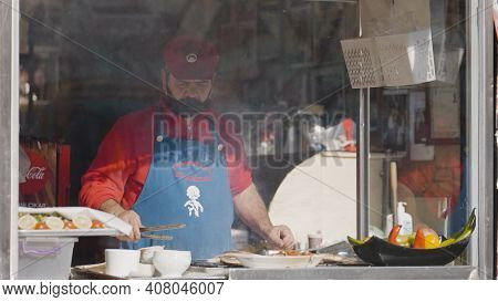 Turkey, Istanbul-december, 2020: Man Roasts Street Food. Action. Cook Cooks Grilled Fish In Street S