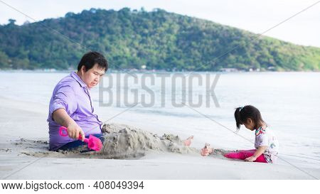 Family Traveled To The Beach On Vacation. Father And Daughter Lounge In The Sand By Beach. During In
