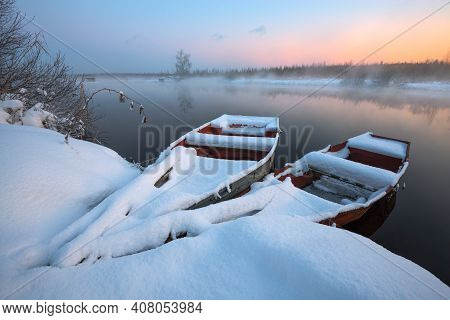 Beautiful Winter Sunrise At The River. The Boats In Snow At The River In The Winter