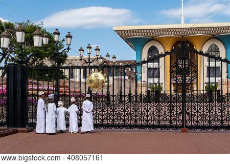Muscat, Oman, 28/01/2020. Muslim Boys Wearing Traditional Kanduras Standing In Front Of The Gate Of