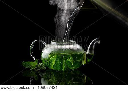 Pouring Hot Water Into A Glass Teapot On A Black Background, Mint Tea